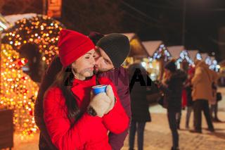 Man and woman embracing, having fun at Christmas fair