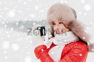 happy woman with film camera outdoors in winter