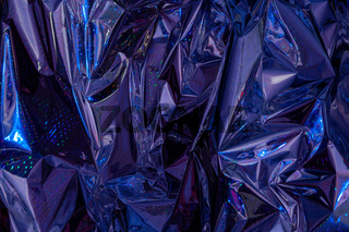 The background of crumpled holographic packaging film with an abstract pattern.