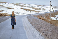 Woman walking along the rural highway