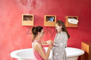 Mutter hilft Tochter beim Bademantel anziehen