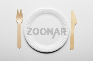 Wooden single use kitchenware and paper plate on white background closeup. Top view