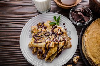 French crepes with chocolate sauce walnuts eggs and flour on wooden kitchen table