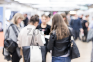 Blured image of businesspeople networking and socializing during coffee break at business event.