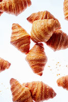 Falling fresh french croissants with crumbs on a light background.