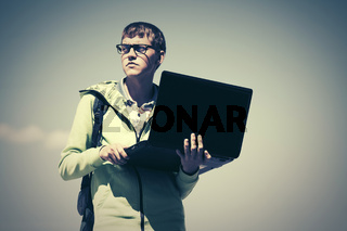 Young fashion man with laptop on city street