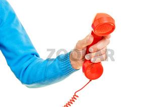 Hand hält ein rotes Telefon als Notruf Konzept