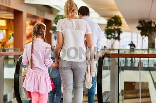 Familie und Kinder fahren Rolltreppe