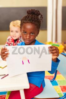 Afrikanisches Mädchen zeigt ein Bild im Malkurs
