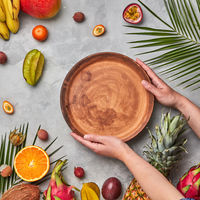 Hands of a woman holding a brown empty plate around a different tropical fruit ripe on a gray concrete background with copy space. Flat lay
