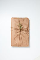 A gift wrapped in craft paper and decorated with flowers on a light background with copy space. Flat lay