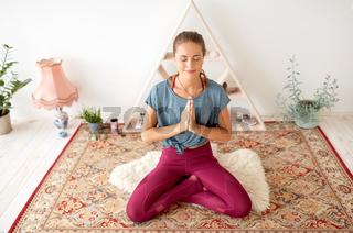 woman meditating in lotus pose at yoga studio
