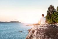 Young Man Meditating on beach.