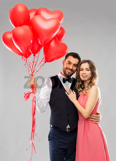 happy couple with red heart shaped balloons