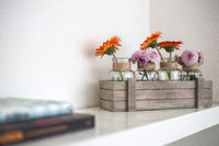 Wooden box with orange and pink flowers on white shelf, white background, modern design