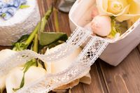 Lace ribbons among flowers and dessert