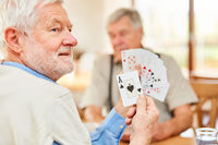 Senior zeigt eine Trumpfkarte beim Kartenspiel