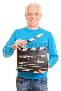 Älterer Regisseur mit Filmklappe beim Filmdreh