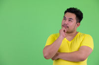 Young handsome overweight Asian man thinking and looking up