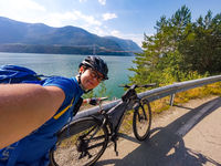 Theme of mountain biking in Scandinavia. human tourist in helmet and sportswear on bicycle in Norway on Hardanger Bridge suspension bridge thrown across the Hardanger Fjord in southwestern Norway