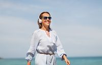 woman with headphones walking along summer beach