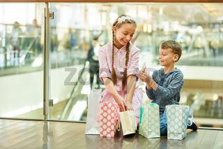 Junge zeigt seiner Schwester ein Geschenk