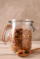 Homemade granola in a storage jar with teh lid open a spoonful in the foreground