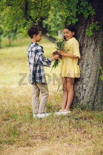 Little boy giving bouqet of flowers to girl.