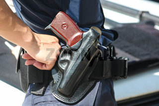 Woman with a gun. Woman policemen with gun in a black holster. Makarov gun in a police holster.