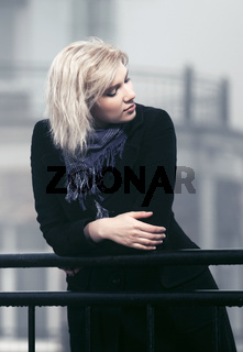 Young fashion woman leaning on railing outdoor
