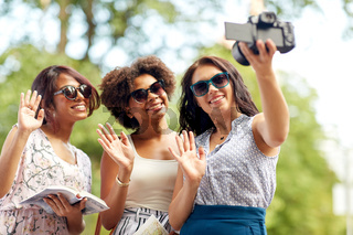 women with map travelling and recording video blog
