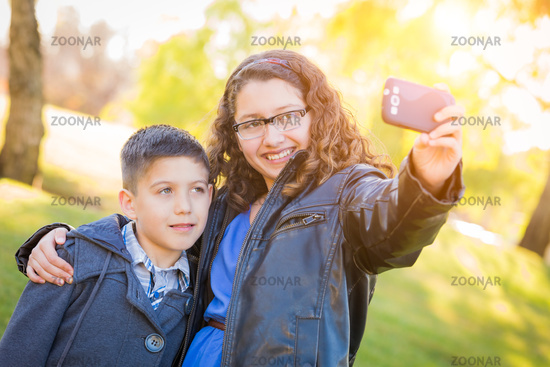 Hispanic Brother and Sister Taking Selfie with Cell Phone