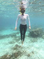 Woman with mask snorkeling in blue sea.