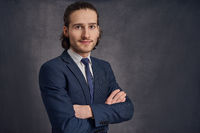 Young man in suit with arms crossed