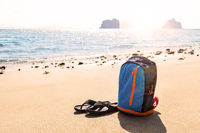 Backpack with flip-flops on beautiful sandy beach.