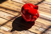 Rotes Sparschwein wirft einen Schatten