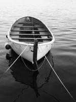 Schwarzweiß-Aufnahme eines leeren Ruderbootes im Wasser