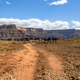 Off road trail with view of canyon under blue sky
