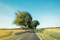 driving fast on road in rural landscape - motion blur