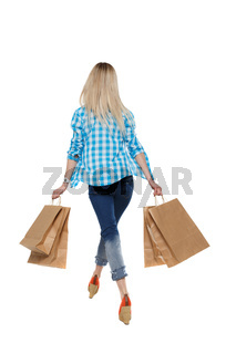back view of going  woman  with shopping bags . beautiful girl in motion.
