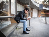 Casual man reading book on bench