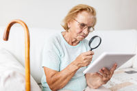 Elderly woman with glasses and loupe using a modern digital tablet