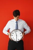 Business man holding wall clock