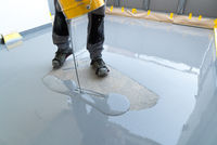 construction worker renovates balcony floor and pours watertight resin and glue before chipping and sealing