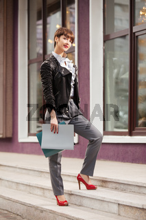 Happy young fashion business woman in leather jacket with a folders walking in city street
