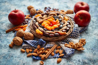 Composition of dried fruits and nuts in small wicker bowl placed on stone table