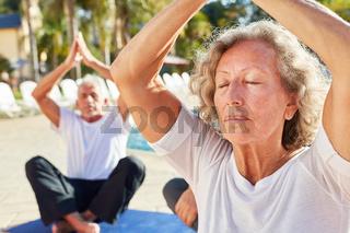 Alte Frau sitzt und meditiert im Spa am Pool
