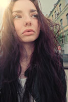 Pensive good looking girl posing with windy hair ouside, wide anglw smartphone lens imitation