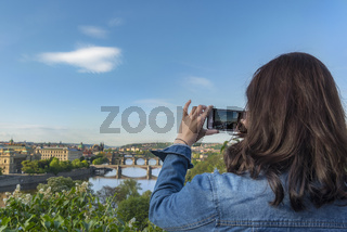 Woman taking photos with phone in Prague