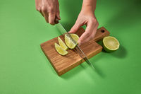 Slices of natural organic green lime, cutting by female hands on a wooden board on green background with copy space.